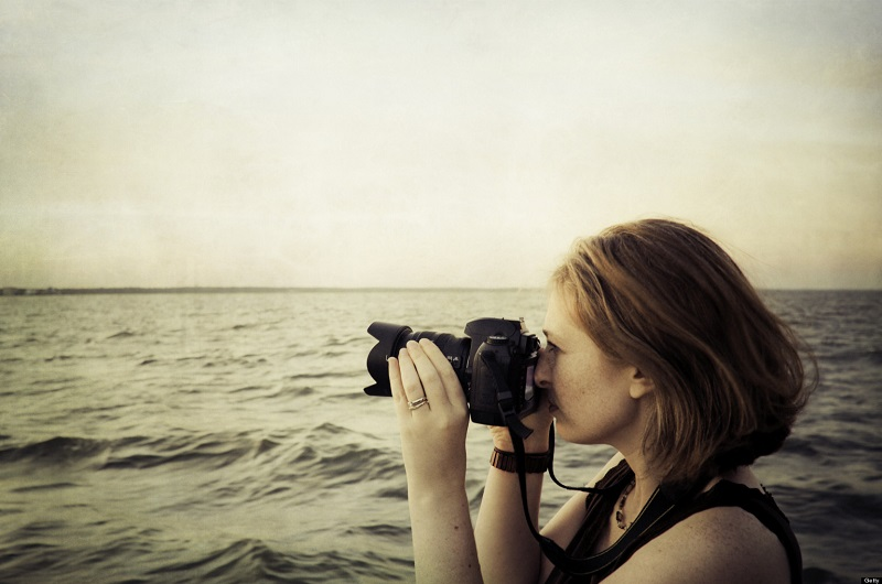 Woman photographer taking picture, holding camera